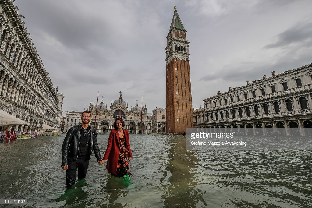 """VENICE, ITALY - OCTOBER 29: A couple of tourists walk in """"Piazza San Marco"""" on October 29, 2018 in Venice, Italy. Due to the exceptional level of the """"acqua alta"""" or """"High Tide"""" that reached 156 cm today, Venetian schools and hospitals were closed by the authorities, and citizens were advised against leaving their homes . (Photo by Stefano Mazzola/Awakening/Getty Images)"""