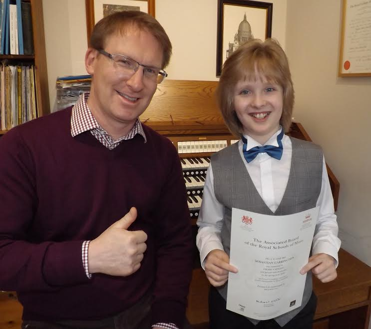 John with Sebastian Carrington, proudly displaying his certificate for Grade 8 Singing (passed with distinction at just ten years old - a remarkable achievement for any boy treble!)