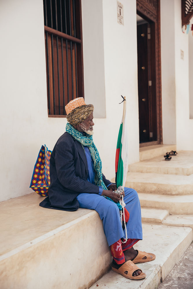 A man sits outside the mosque.