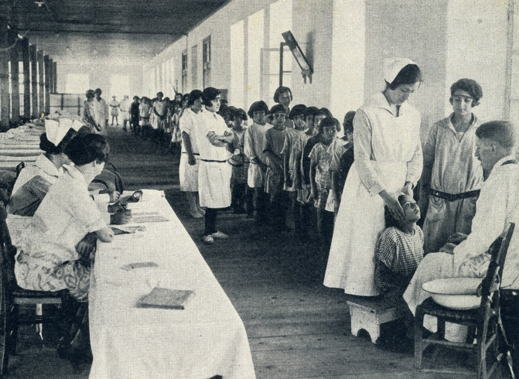 A doctor and nurses conduct medical examinations in an orphanage hall. Some children received daily medical care, depending upon their health conditions.