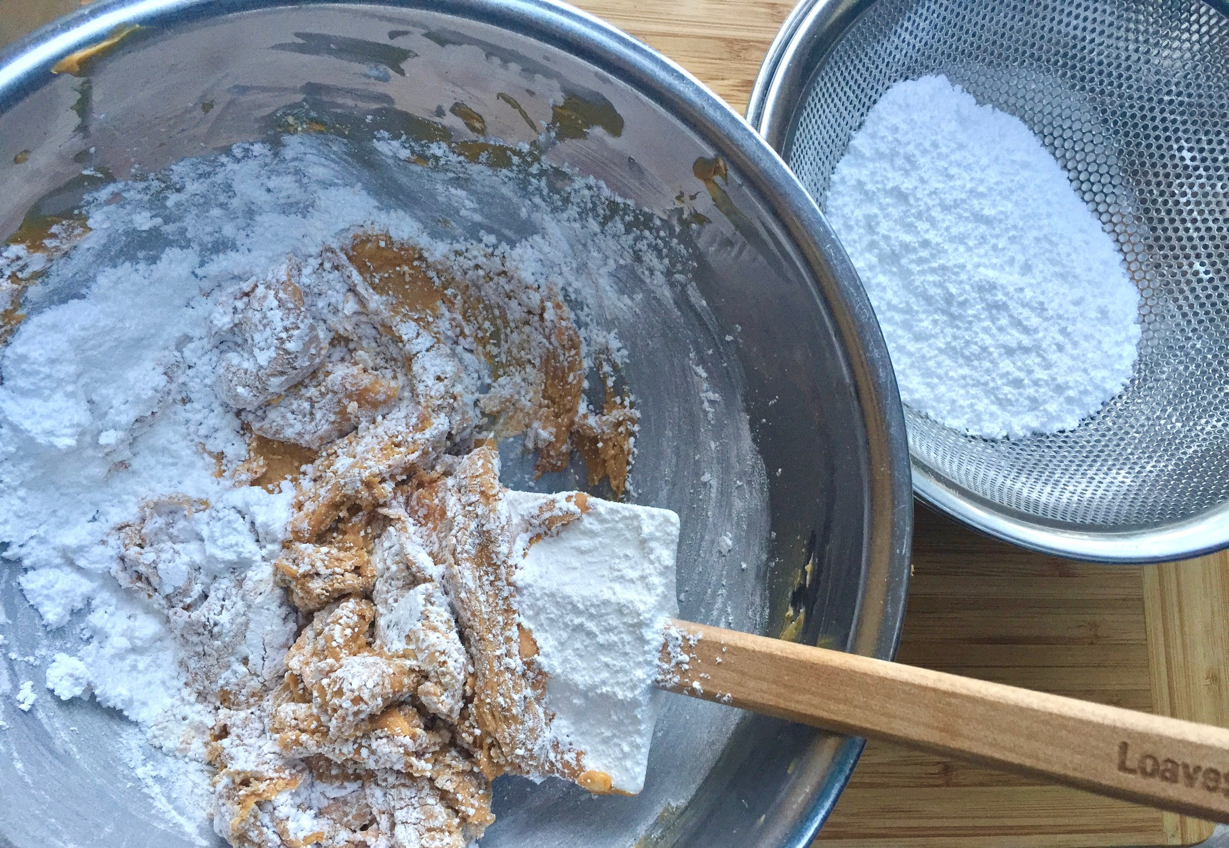 Mixing confectioners sugar into the peanut butter mixture.