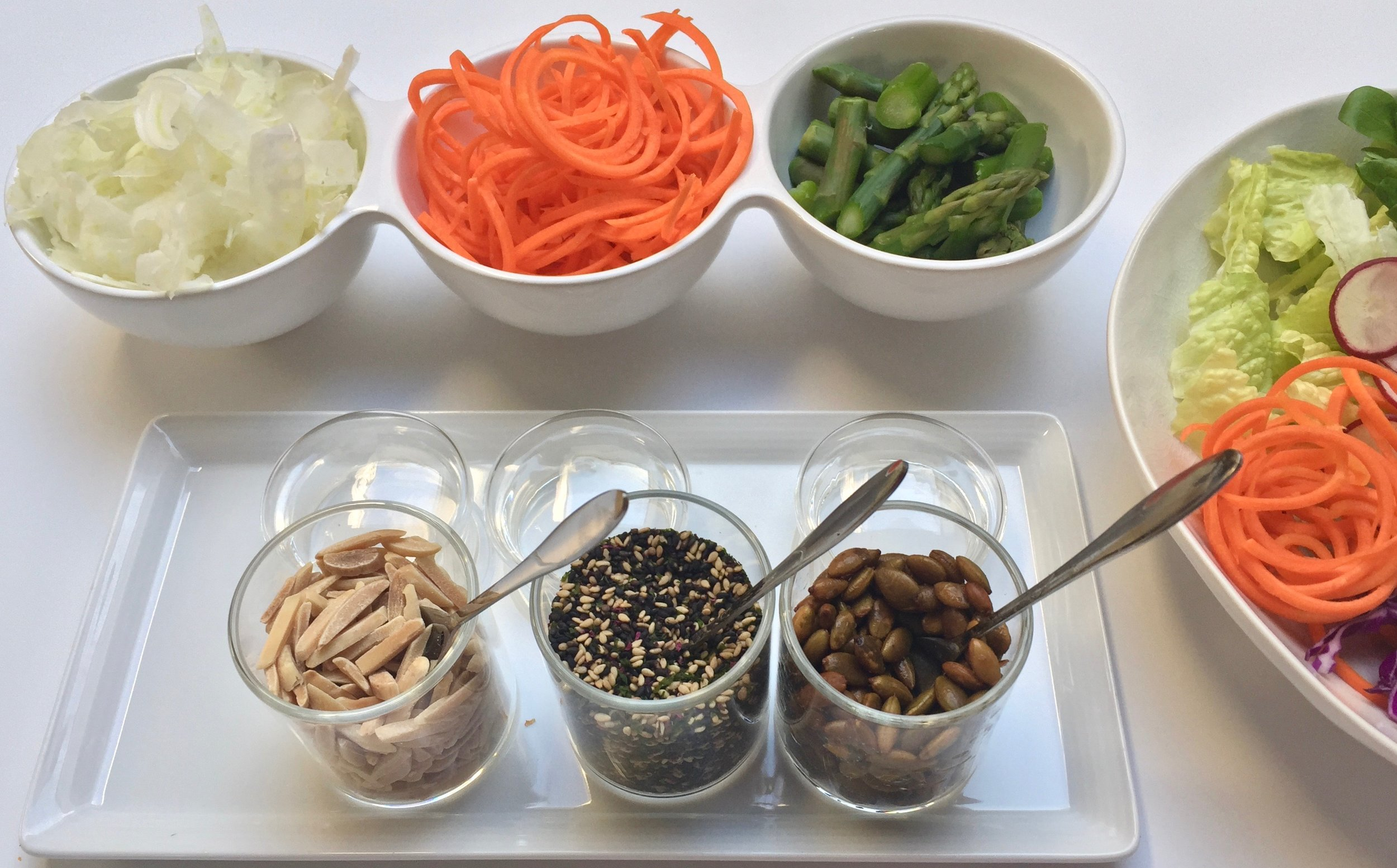 It's a Buddha Bowl Bar! Some components to add to your bowl - raw shaved fennel, pickled carrot spaghetti and blanched asparagus. To add some crunch we offered toasted sliced almonds, black & white sesame seeds with sea vegetables and toasted pumpkin seeds.