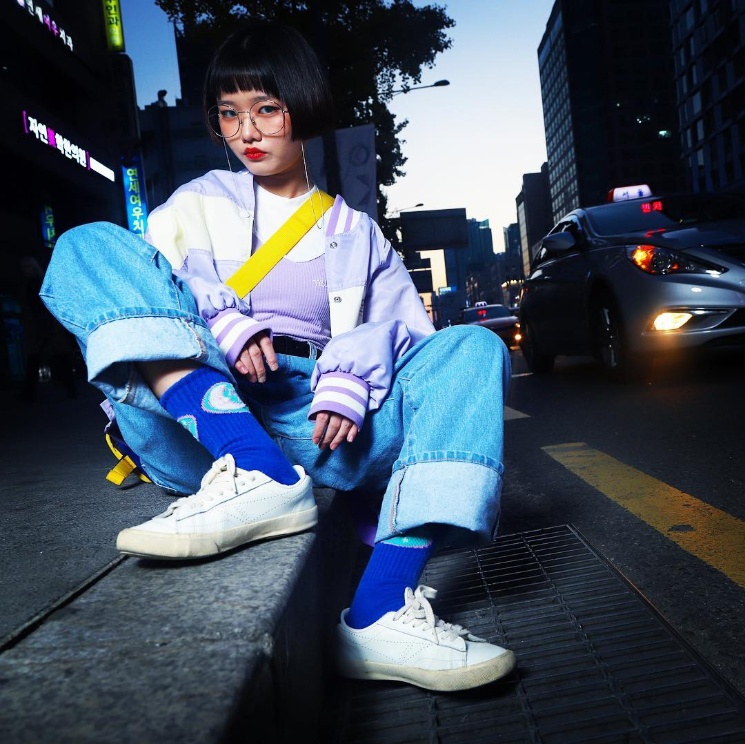"""CAPTION: A young  paepi  middle school student who makes her own glasses accessories and who plans to open an online shop of her goods poses for the camera in Hongdae. Between her haircut, retro glasses,  sukajan  jacket, retro jeans, socks, and old-school shoes, she is a good channeller of the Korean """"boko""""     retro trend."""