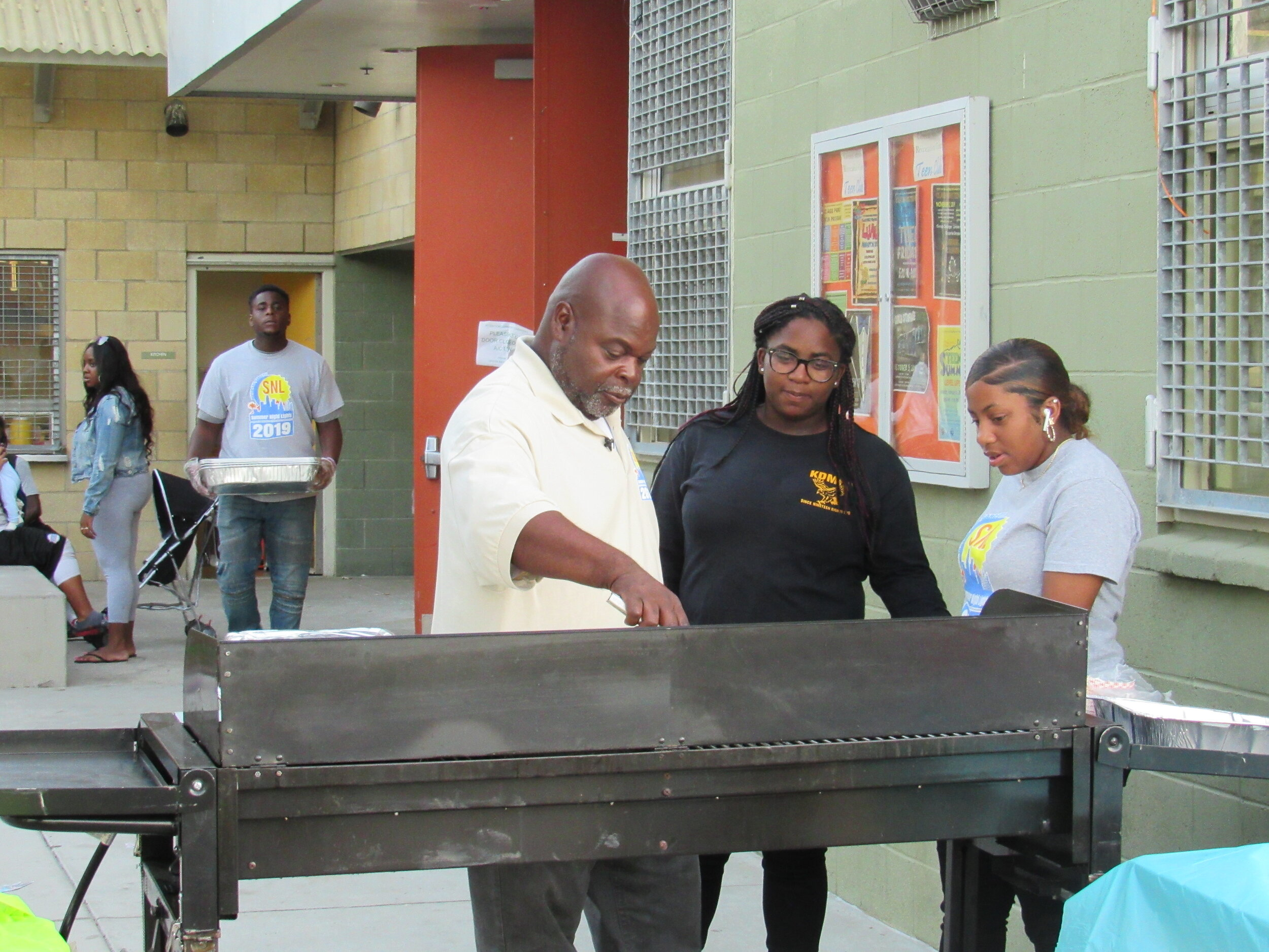 Larry managing the grill with neighborhood youth.