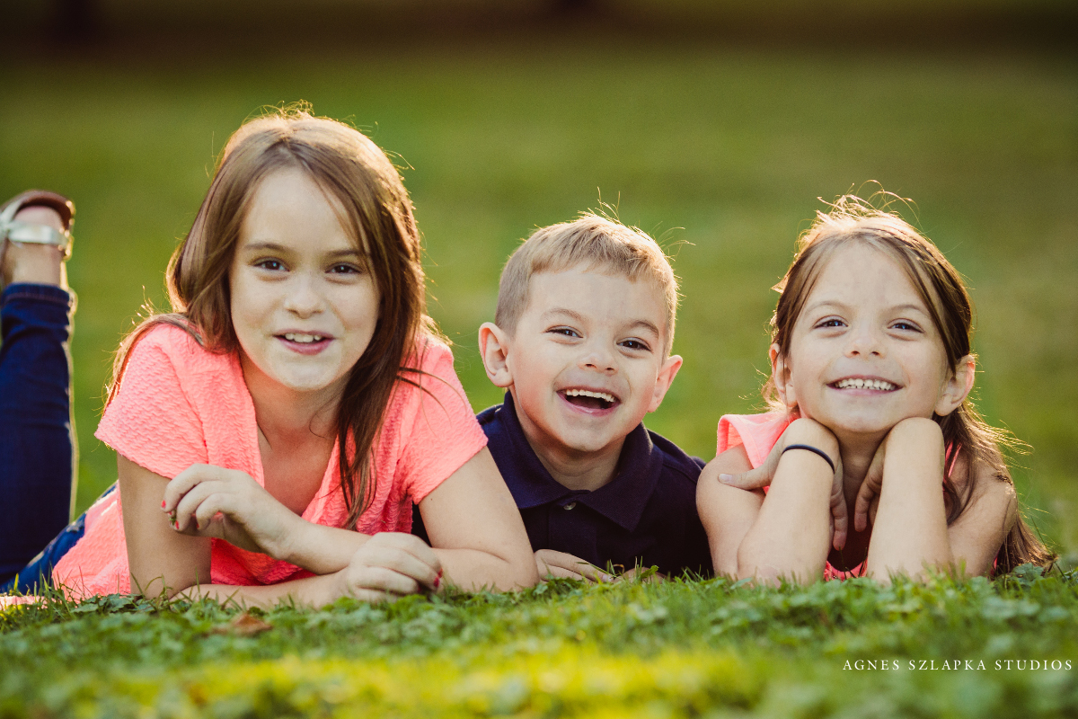 three siblings laying on grass | cleveland family photos