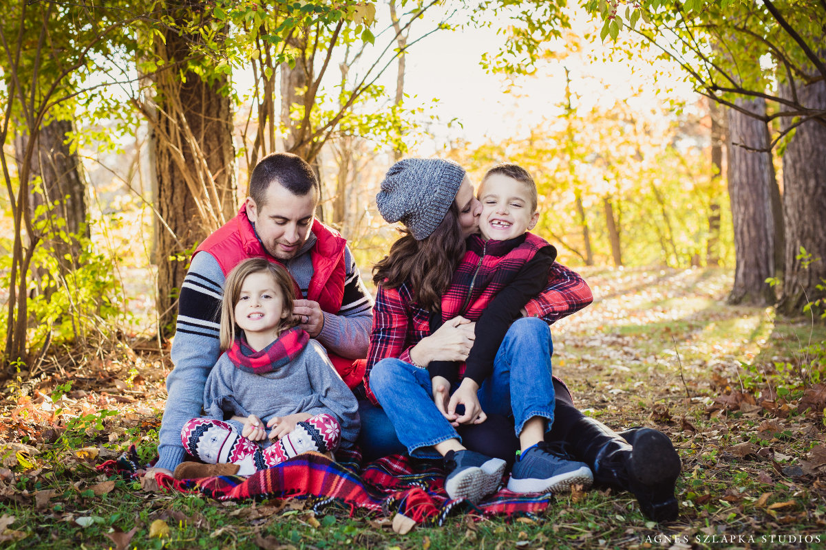 parents with two kids loving their children and laughing on blanket | cleveland, ohio lifestyle family photos