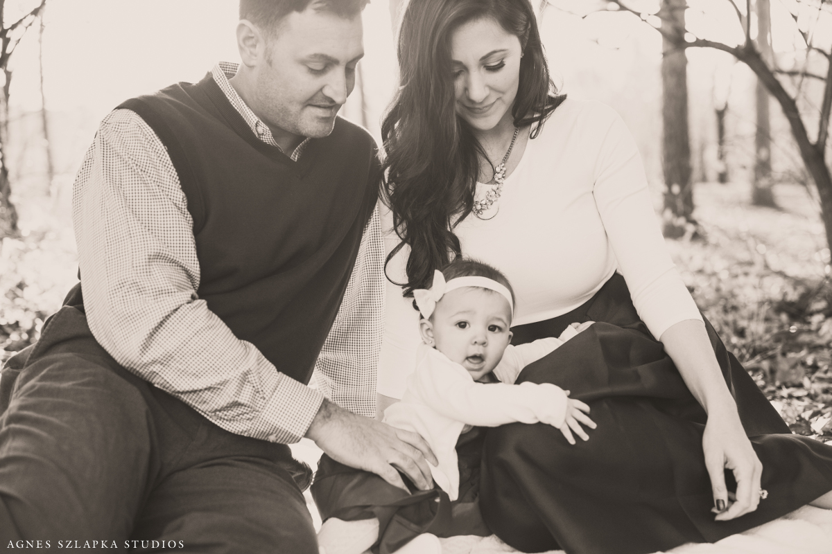 parents with baby girl relaxing in park | cleveland, ohio lifestyle family photographer