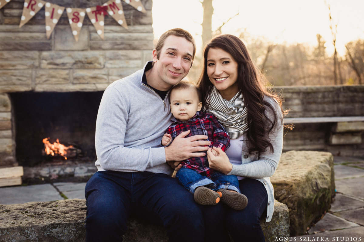 parents with infant son by outside fireplace | cleveland, ohio family photographer