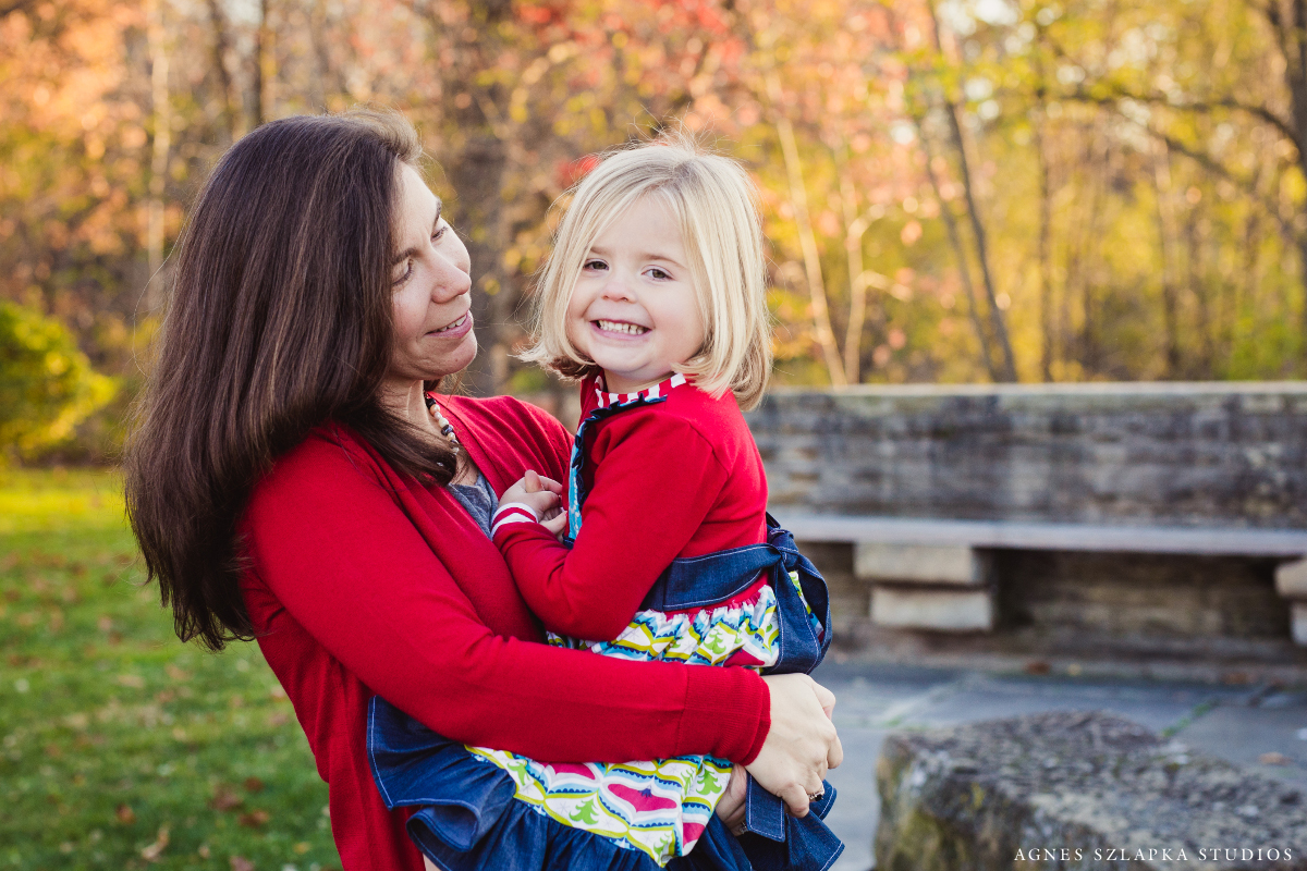 mother holding three year old daughter in arms smiling | cleveland, ohio family photography