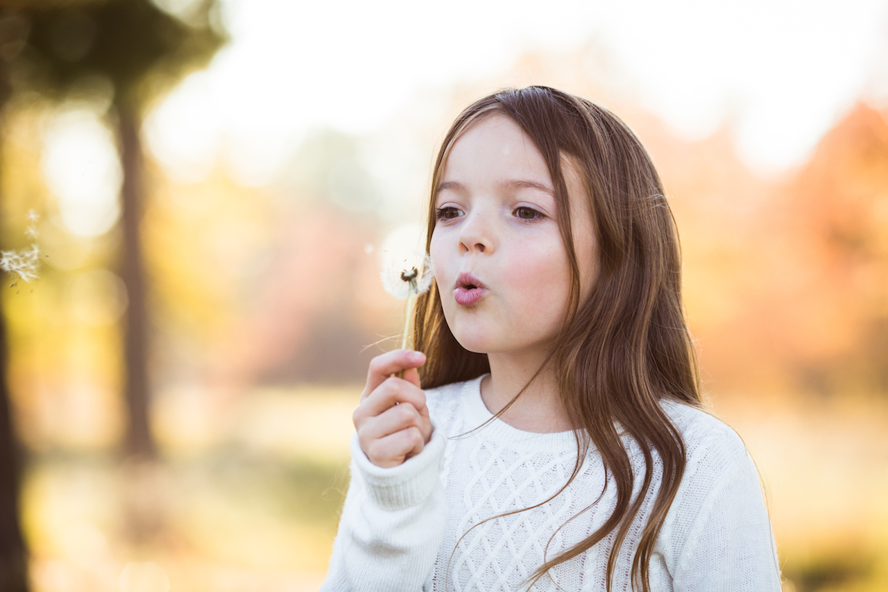 preteen girl blowing dandelion in park during fall | cleveland, ohio kids photography