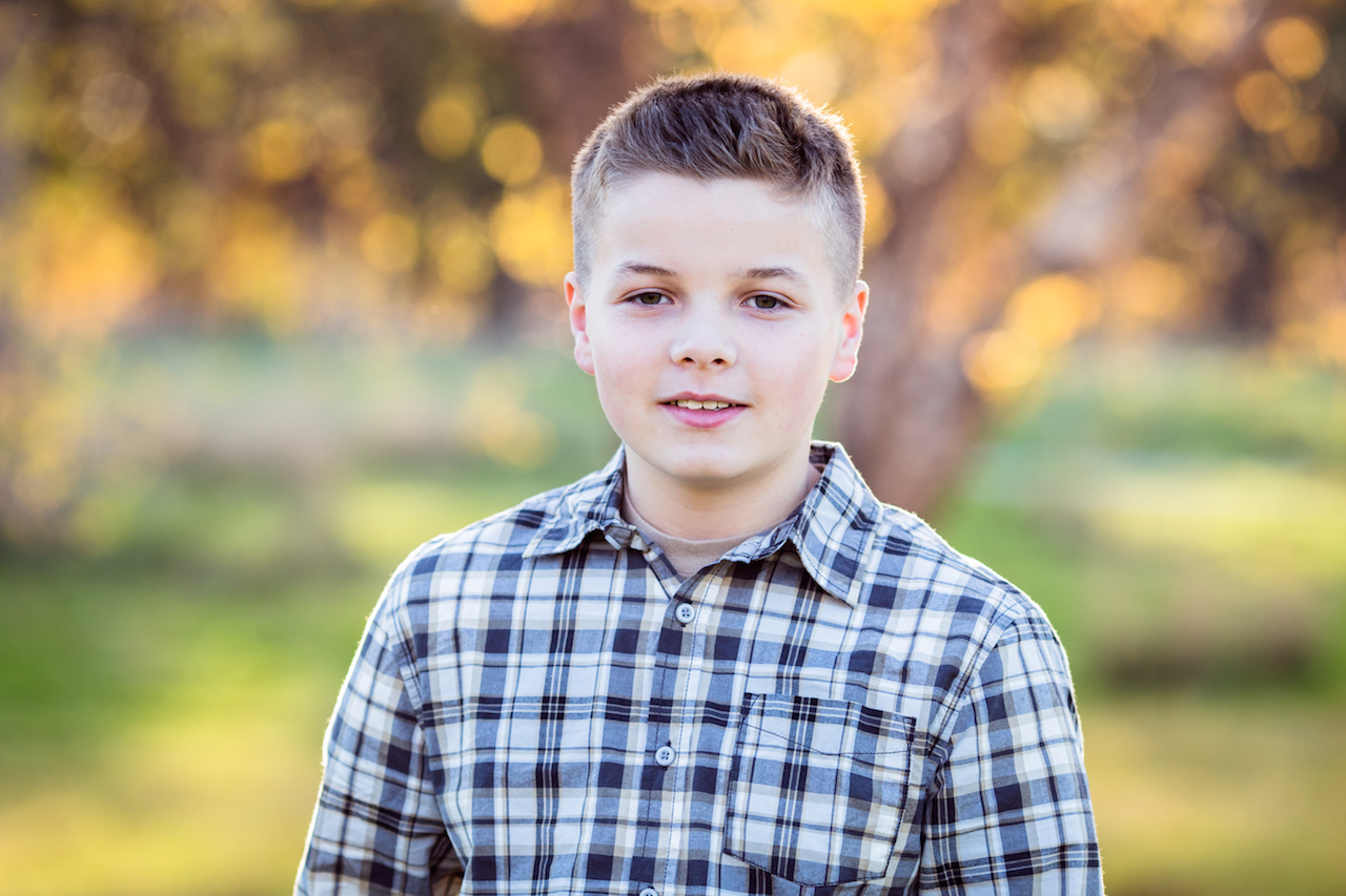 preteen boy in plaid shirt in park during fall | clevealnd, ohio child photography