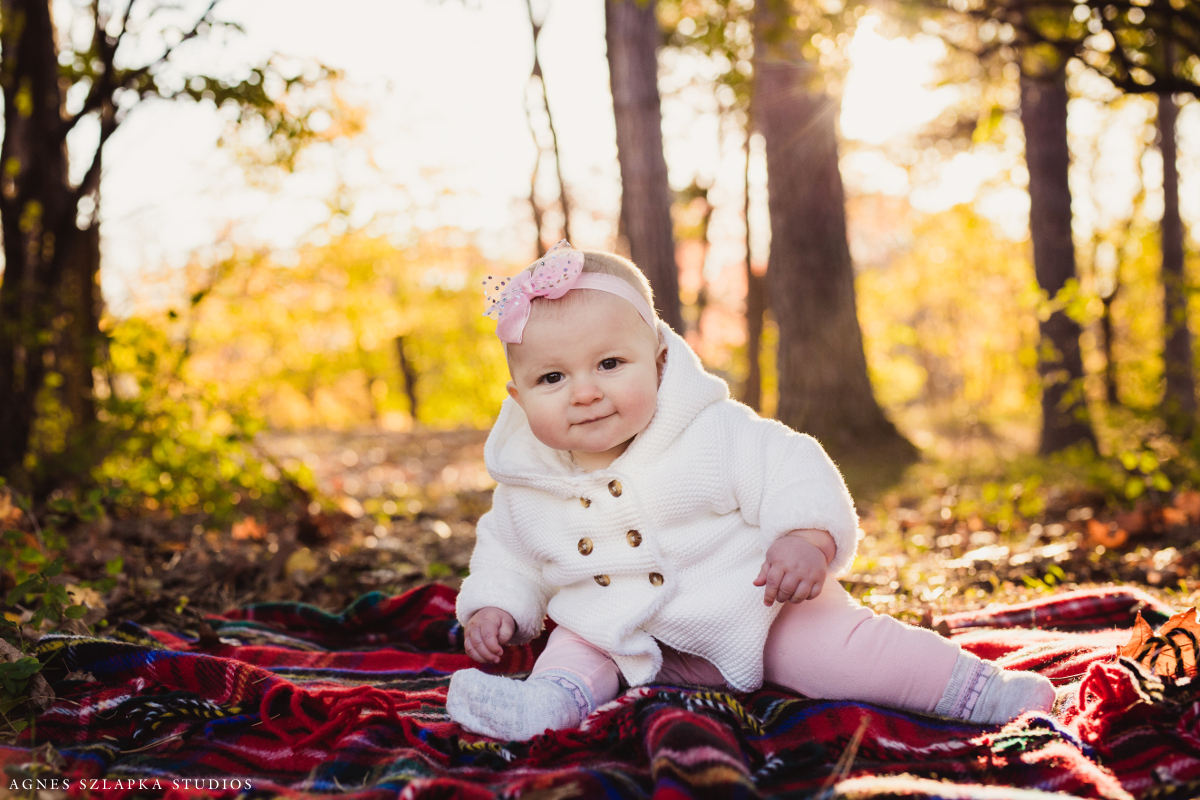 baby girl in white sweater sitting on red blanket | cleveland, ohio kids photography
