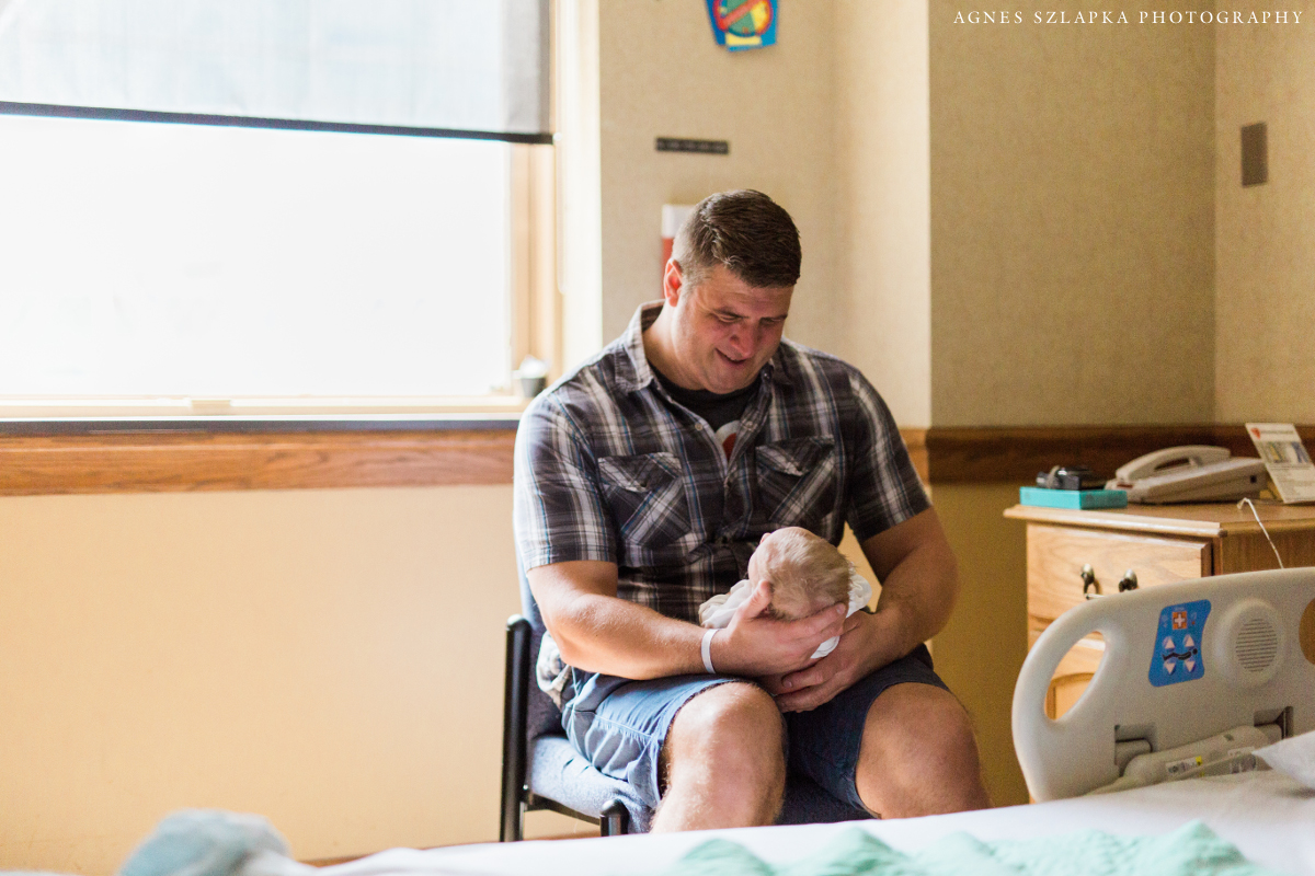father holding newborn son on his lap in hospital | cleveland, ohio baby photographer