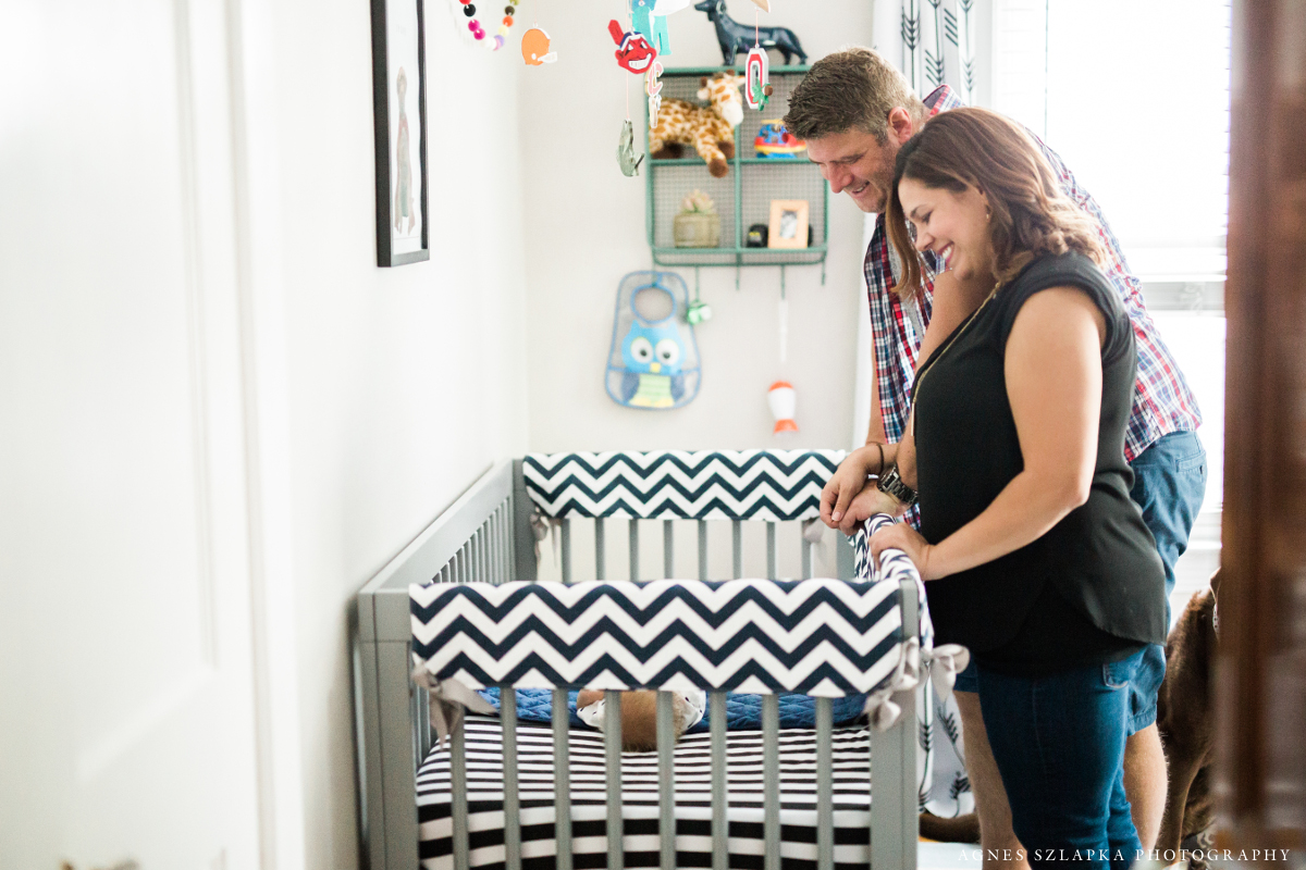 parents looking down at baby in crib | cleveland, lifestyle newborn portraits