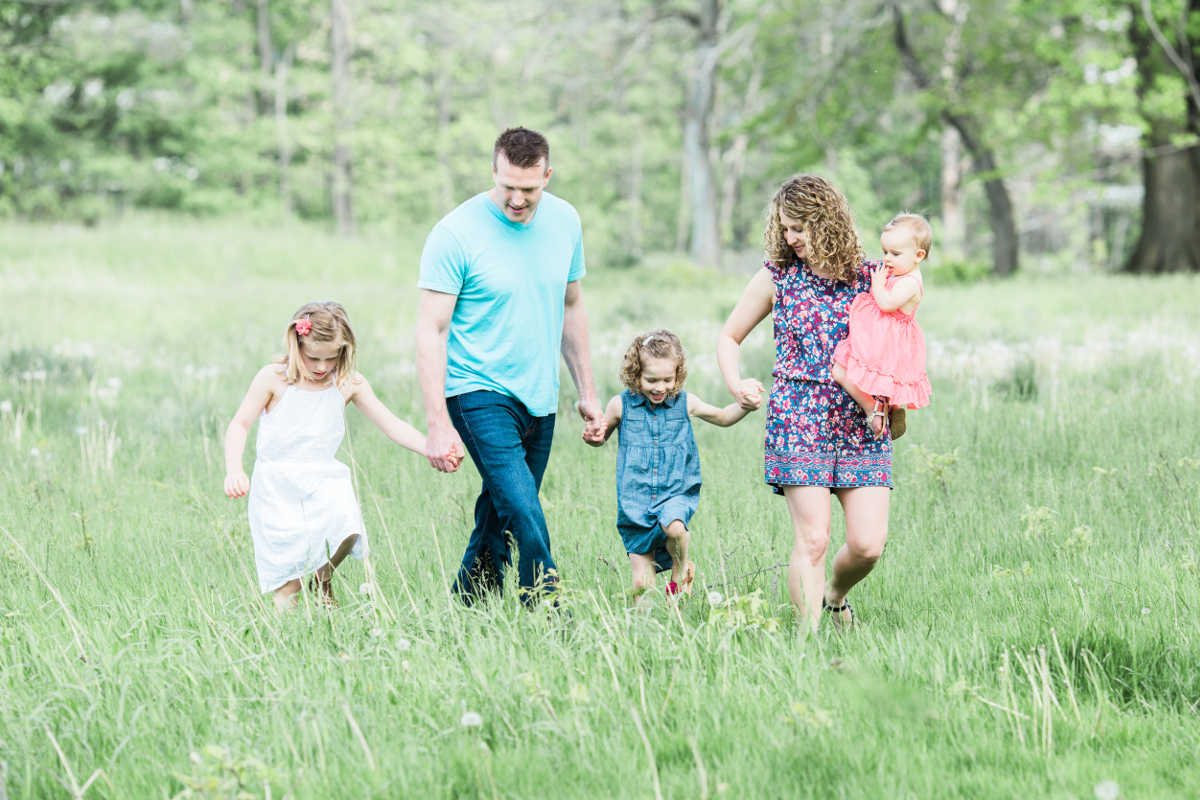 parents with three daughters walking and holding hands | cleveland, ohio lifestyle family photographer
