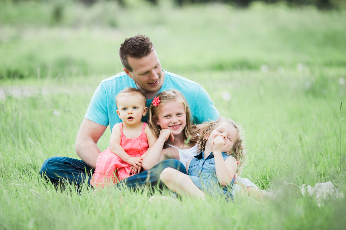 father with three daughters sitting on ground outdoors | cleveland, ohio family photography