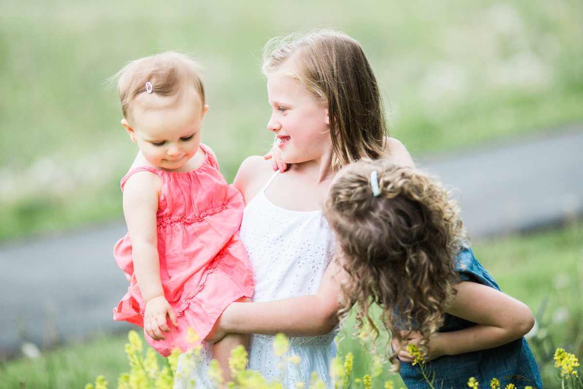 older sisters observing baby sister | cleveland, ohio family photos