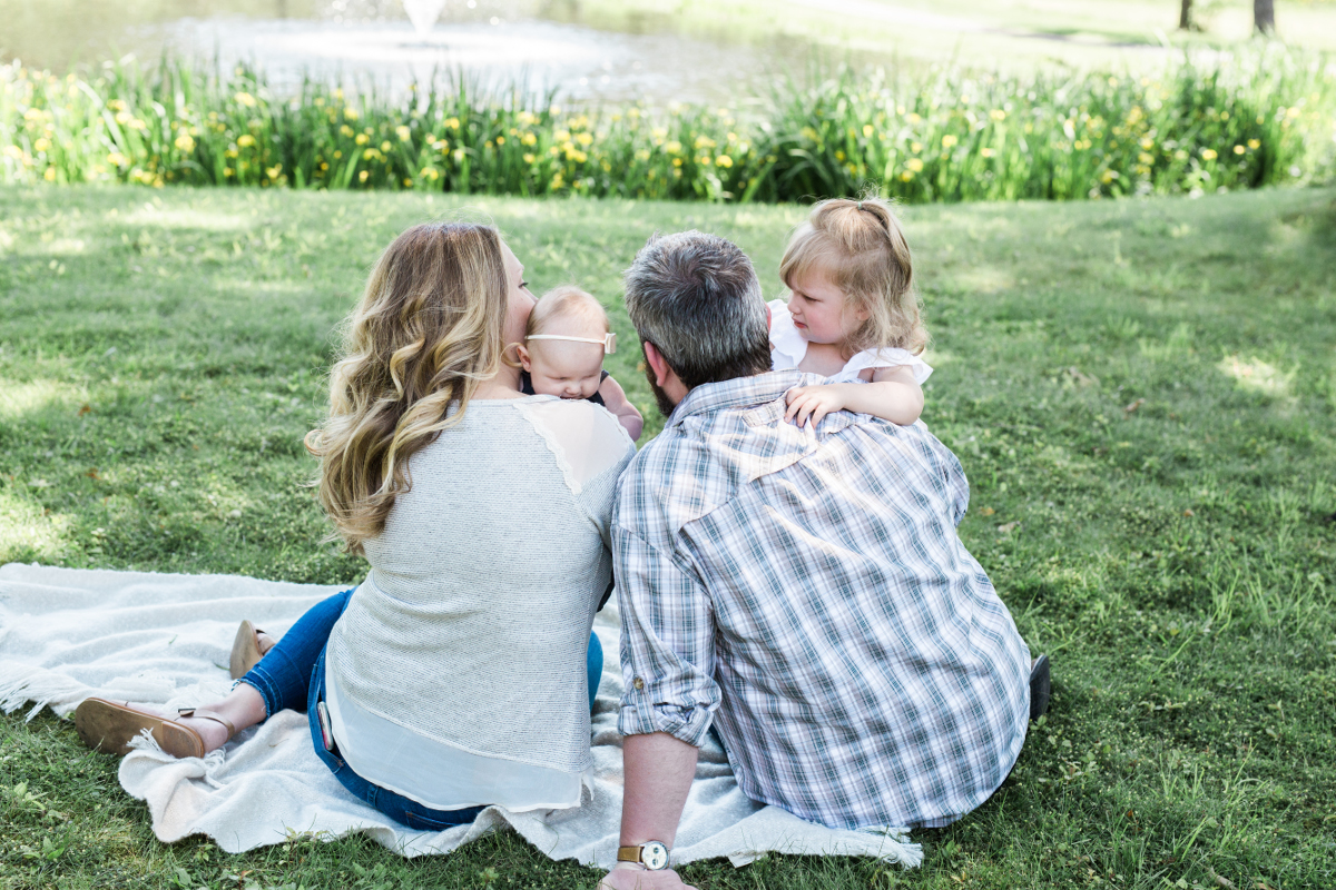 family with two daughters looking at pond | cleveland, oh lifestyle family photographer