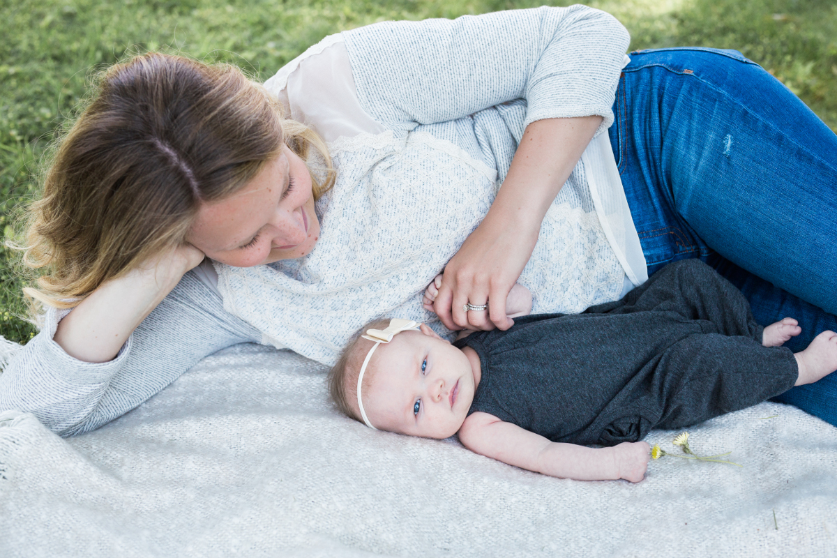 mom of two kids laying on blanket with infant | cleveland, oh family photos
