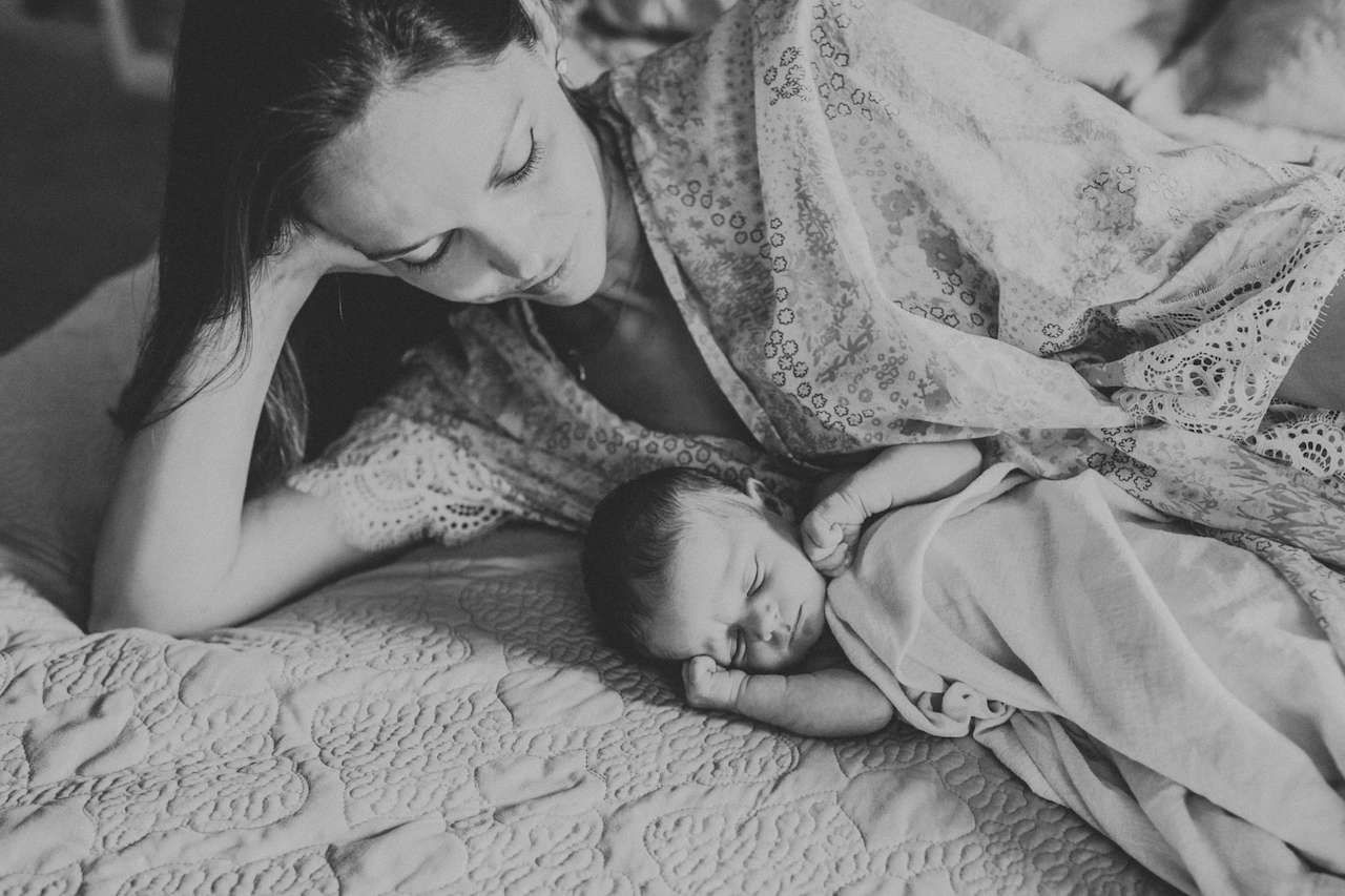 mom on bed with newborn baby girl | cleveland, ohio family photography