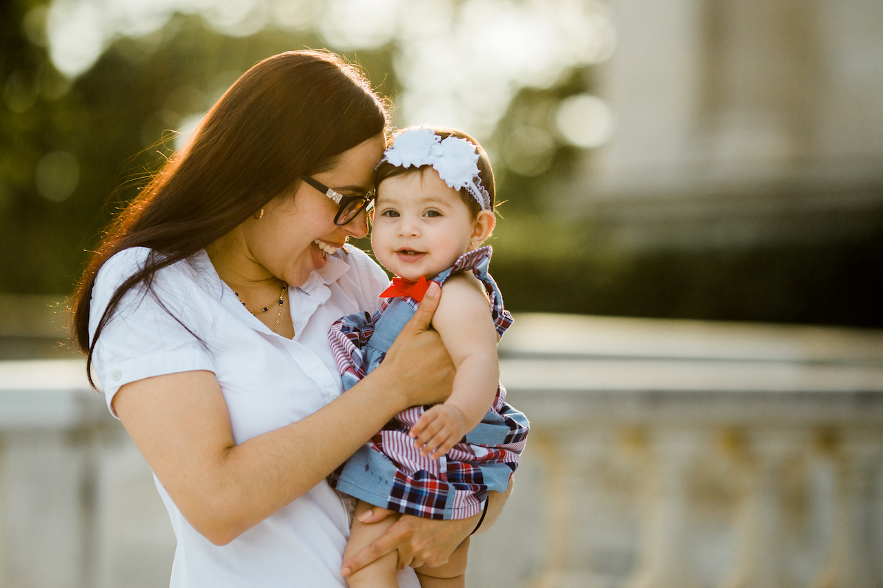 mom holding infant girl in arms smiling | cleveland, family lifestyle photographer