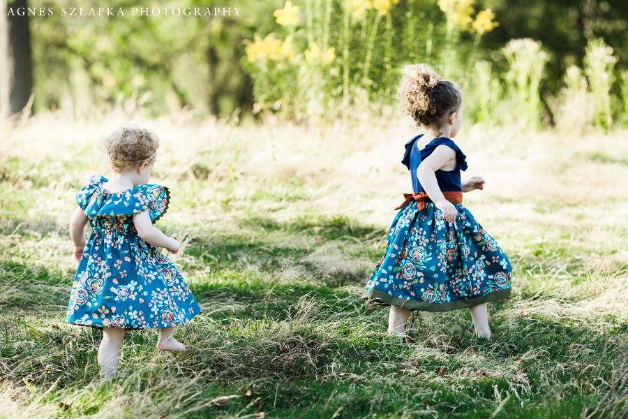 two sisters with matching dresses skipping on grass | cleveland, OH family photographer