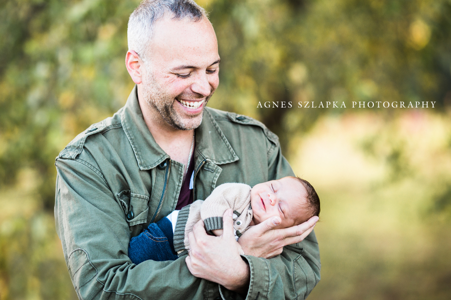 dad holding sleeping infant baby son in park | clevaealnd, OH newborn photography