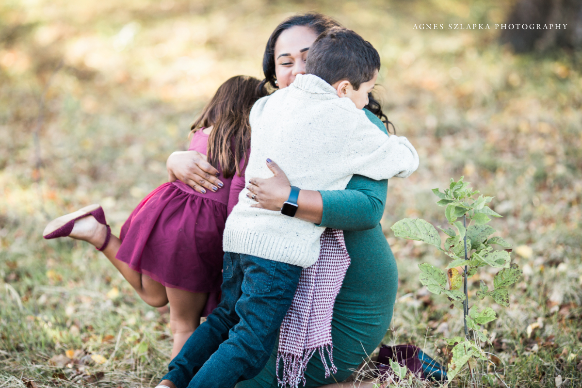 two younger kids hugging their mom in park | cleveland, OH family photographer