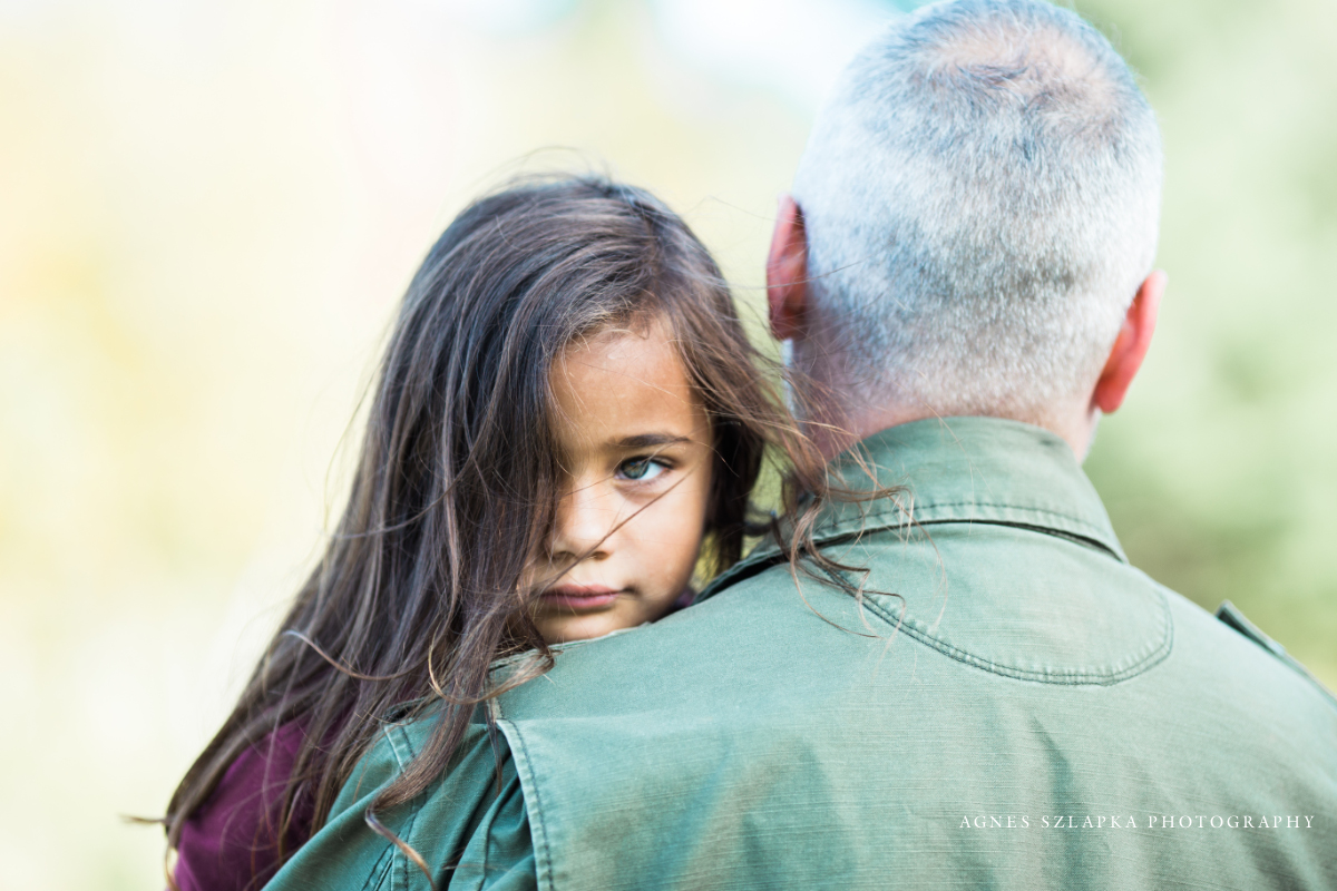 daughter in dads arms overlooking shoulder   cleveland, OH lifestyle portraits
