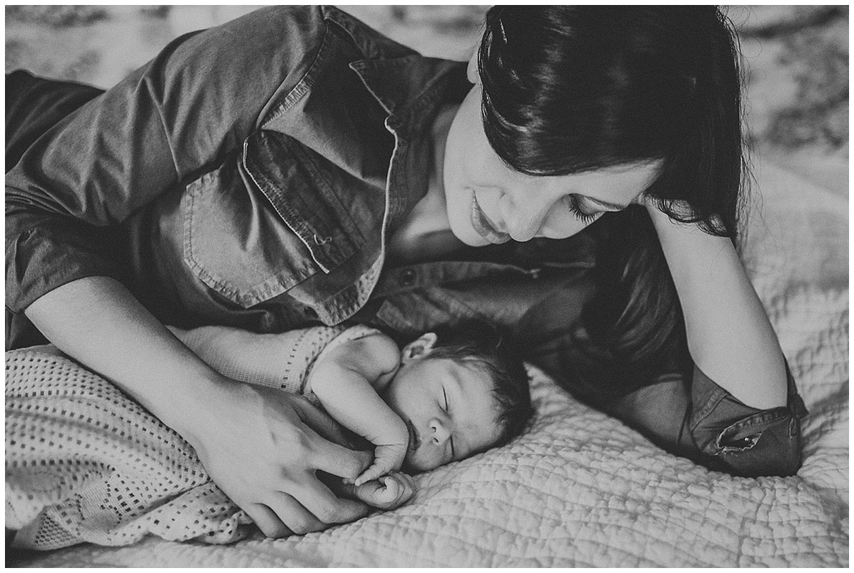 mom and sleeping infant baby boy laying on bed | cleveland, OH newborn photography