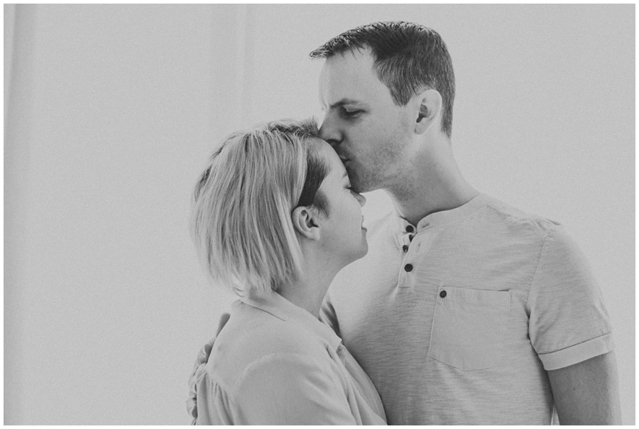 dad kissing mom on forehead in bedroom | cleveland, OH newborn photography