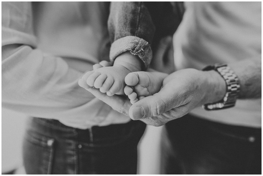 dad holding tiny baby feet of daughter | cleveland, OH lifestyle newborn photographer