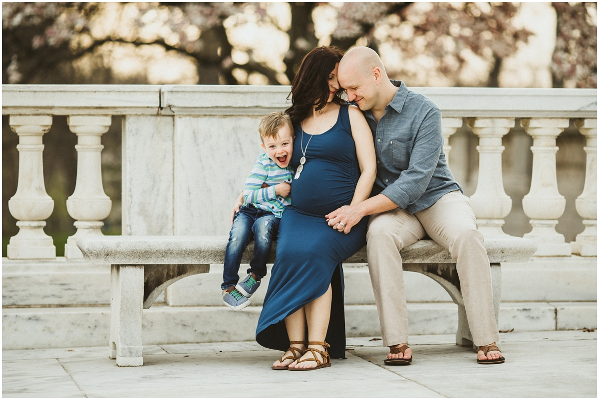 family of three sitting on bench at art museum | cleveland, OH maternity photographer
