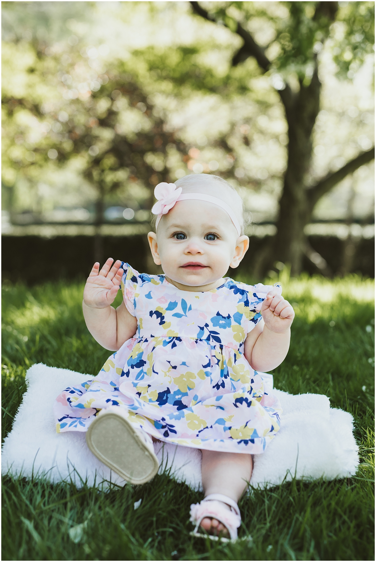 one year old girl sitting on grass with bow | cleveland, OH family photographer