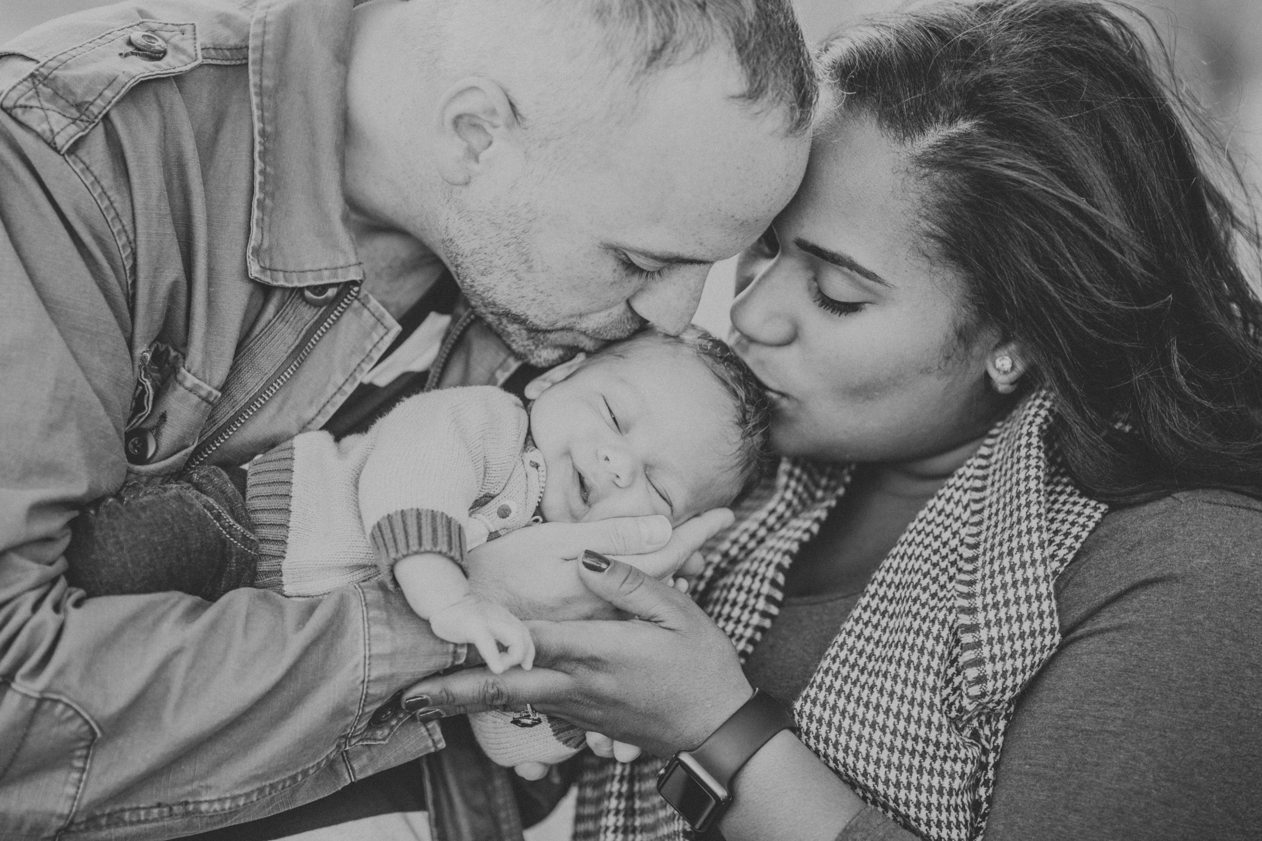 newborn baby son being kissed by mother and father | Cleveland, OH family photographer