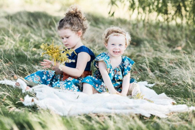 two little sisters playing with yellow flowers on blanket | Cleveland, OH family photographer