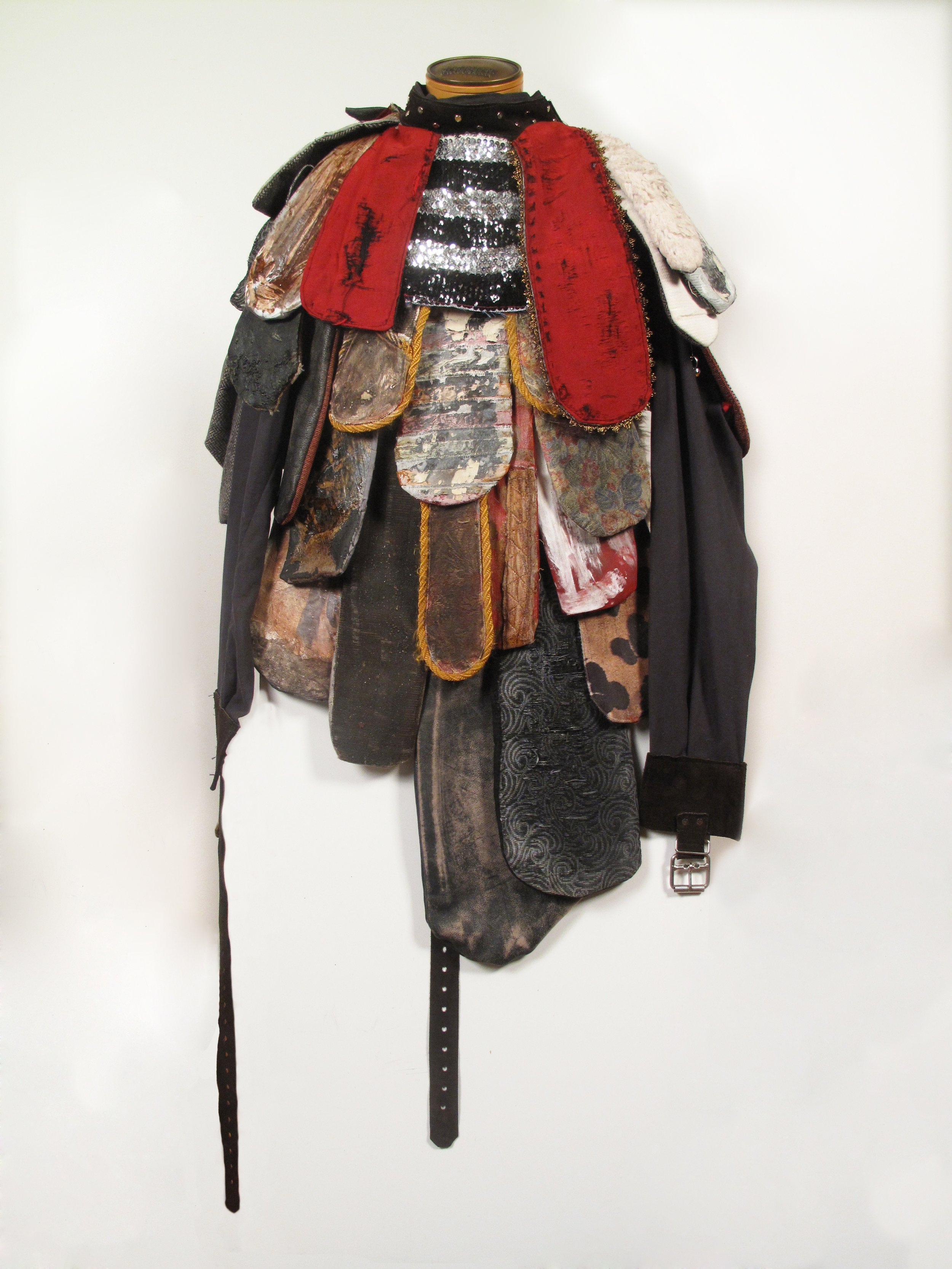 """Jefferson Pinder  Magical Negro (Egungun)   2013 straitjacket, acrylic, fabric, collage transfer, copper leaf, sequins, fencing mask, central armature 48"""" x 22"""" x 12"""""""