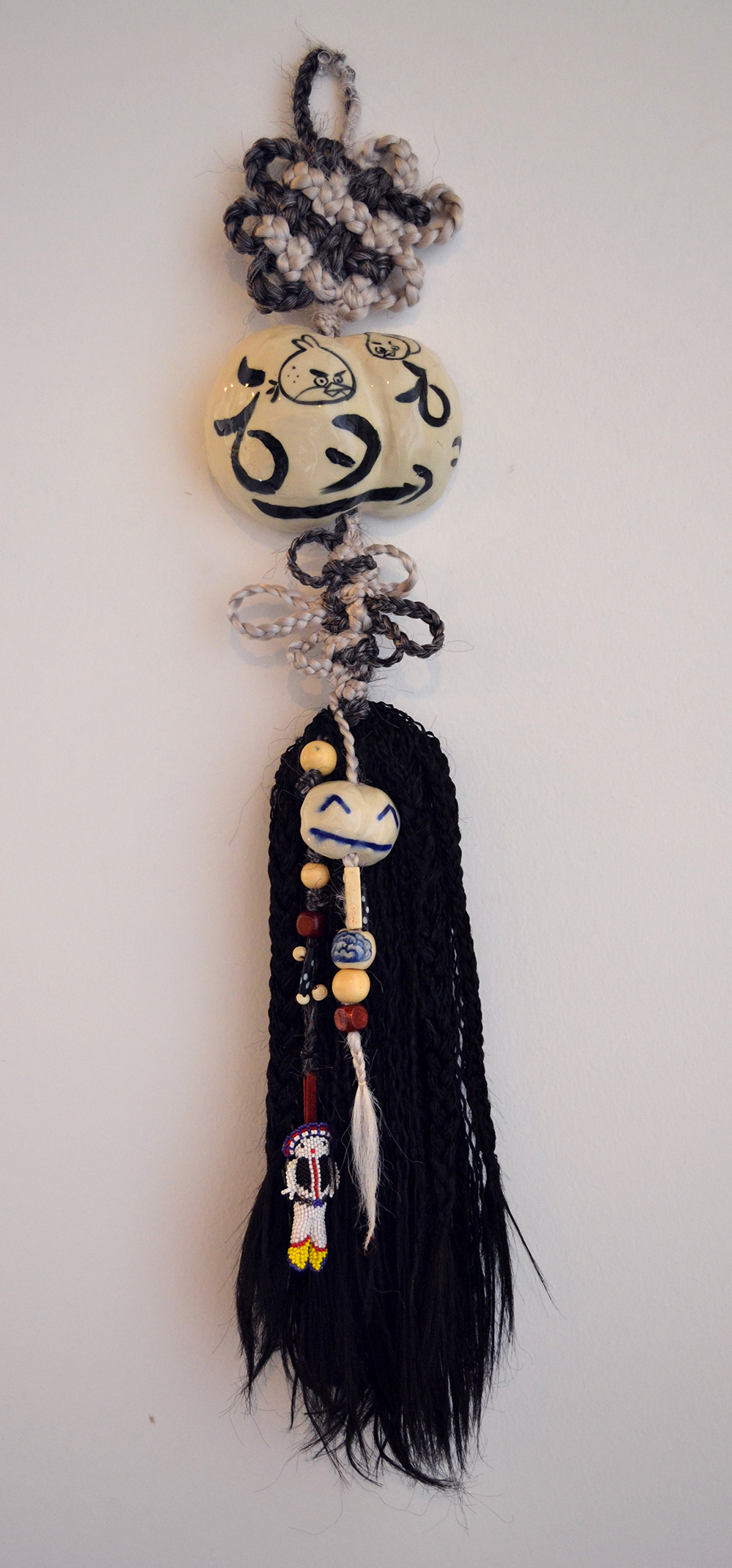 "Jiha Moon  Harley Crow  Ceramic, hand-knotted synthetic hair, wooden beads, found objects 28"" x 5"" x 2.25"" 2013"