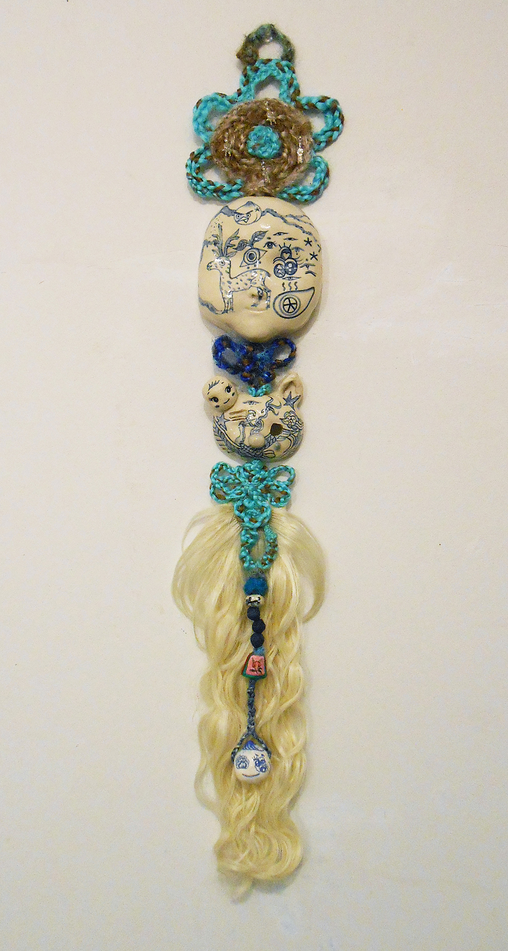 "Jiha Moon  Moonface  Earthenware ceramic, hand-knotted synthetic hair, found objects, wire 33"" x 6.5"" x 2"" 2015"