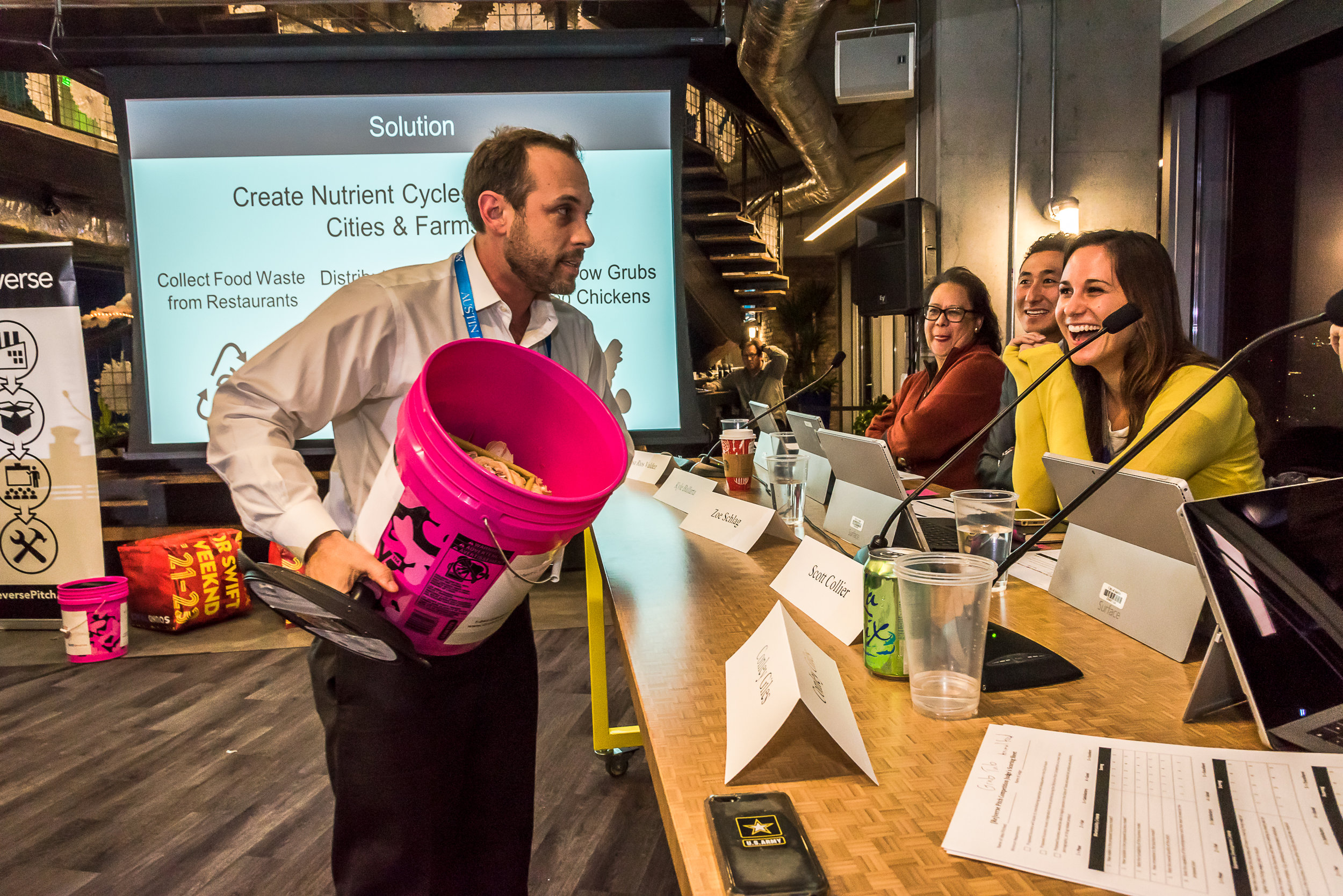 Robert Olivier of GrubTubs shows a sample food scrap collector to the 2016 [Re]verse Pitch judges. Judges pictured, from front to back: Zoe Schlag, Kyle Ballarta, and Rosa Rios Valdez. Photo credit: Michael Knox