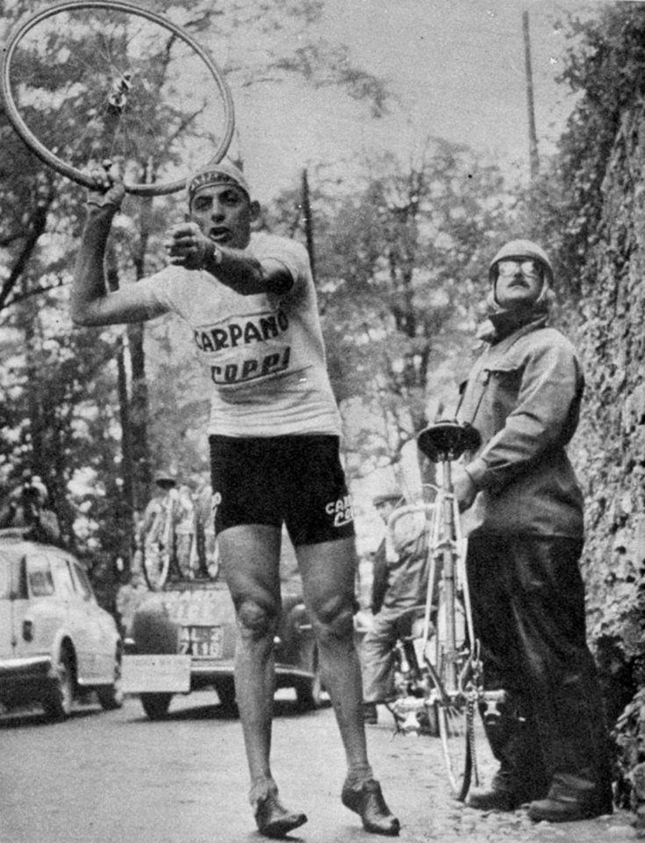 Coppi said YOU, YOU GIVE ME THAT WHEEL RIGHT NOW!!!! The bro next to him is trying not to look at Coppi's huge thighs and tiny ankles, or notice that he's teetering like a crane.