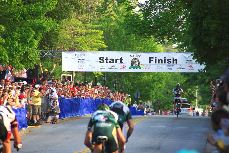 """For the win"" I like the different point of view. Typically a finish line shot is taken with the riders approaching. I like the way this one turned out because it still tells the story of this race as it ends. The spectator excitement, the winner and the ensuing sprint for second."