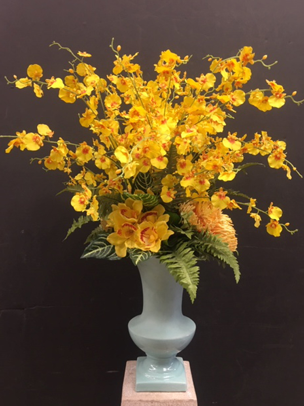 Mixed gold orchids in turquoise vase