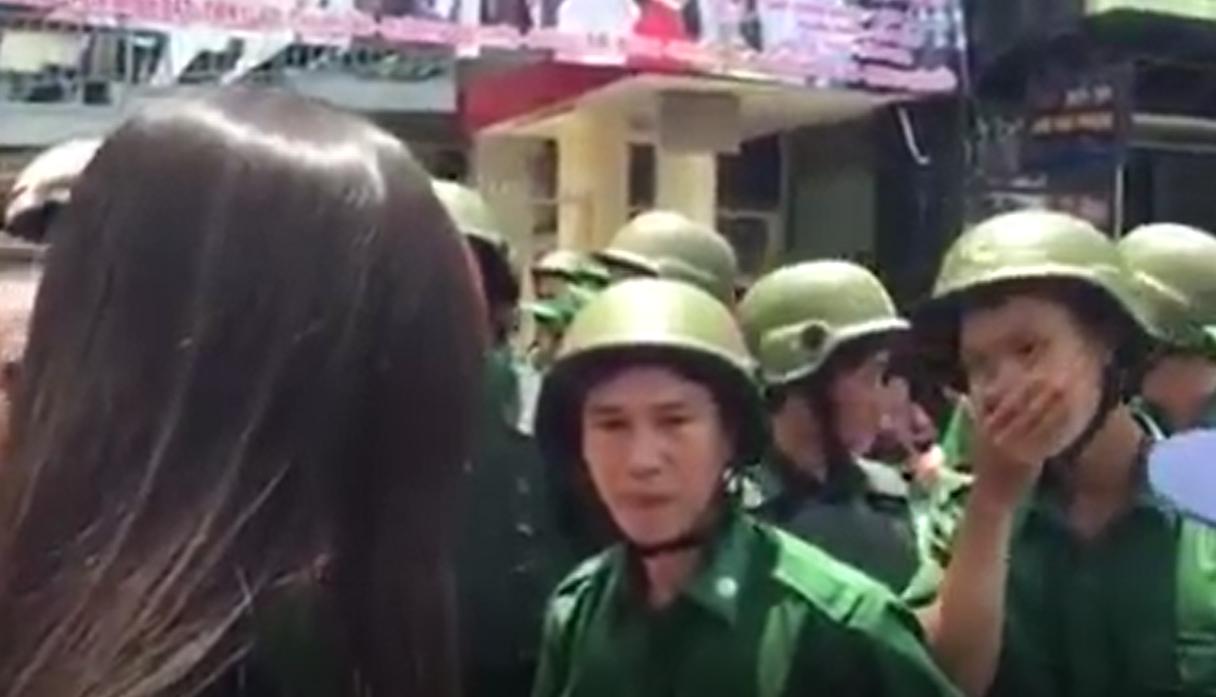 Một người công an đã đưa tay giữmiệng để ngăn đi tiếng bật trước lời nói dõng dạc, chính xác của dân.