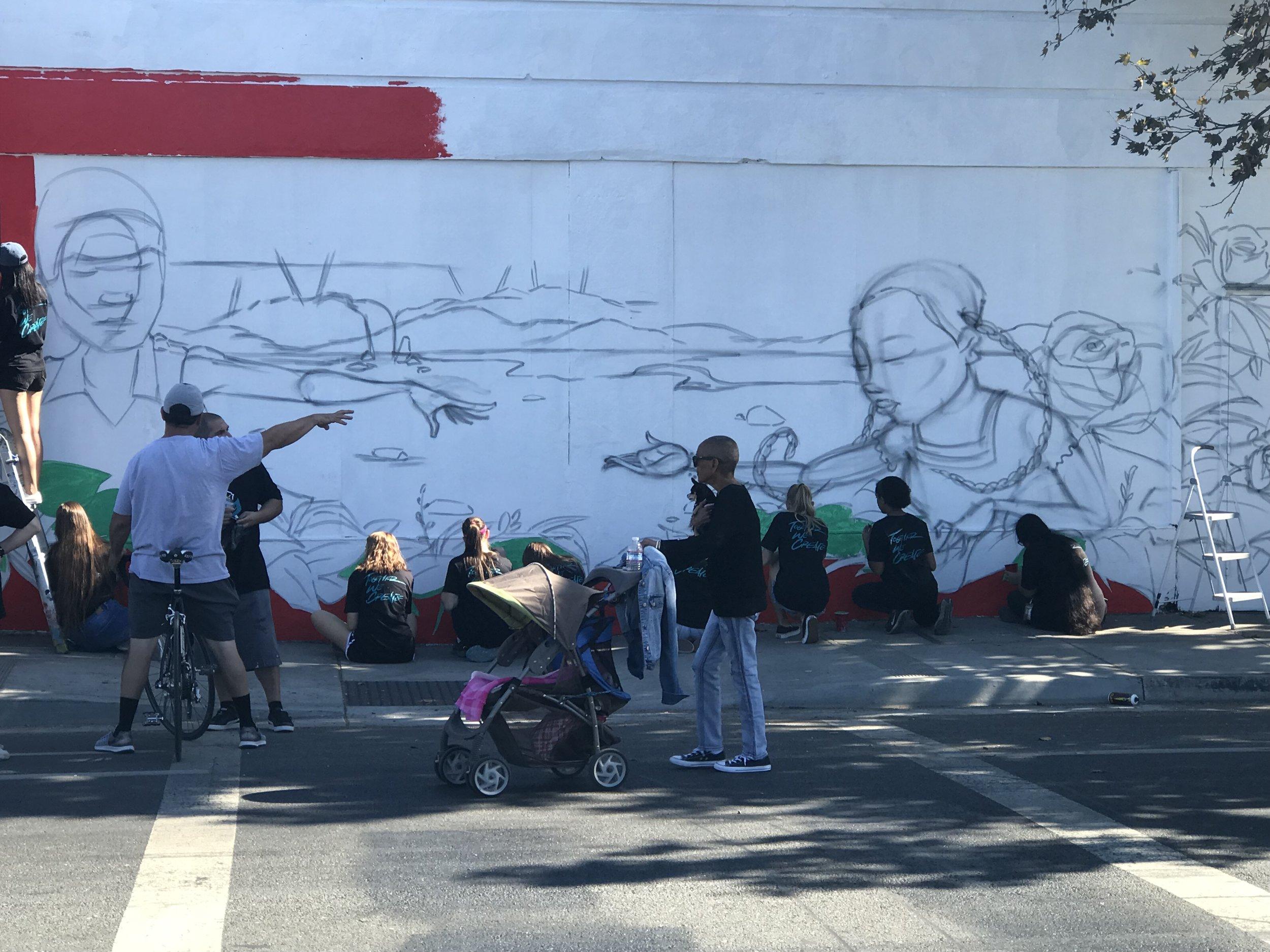 Các nghệ nhân đang vẽ tranh trên tường thành phố.