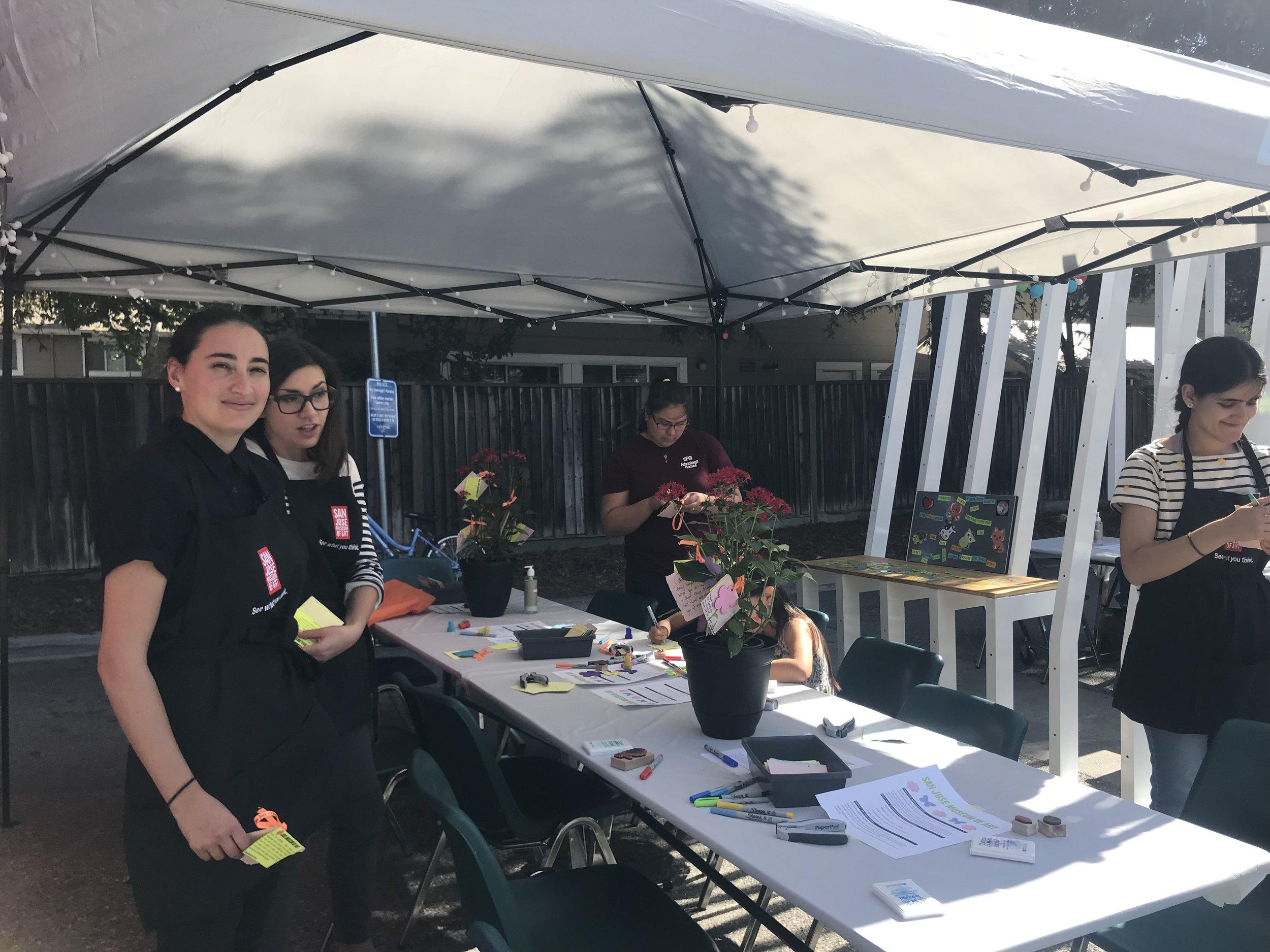 Nhân viên trong gian hàng trồng hoa trên giấy đang chào đón quan khách.