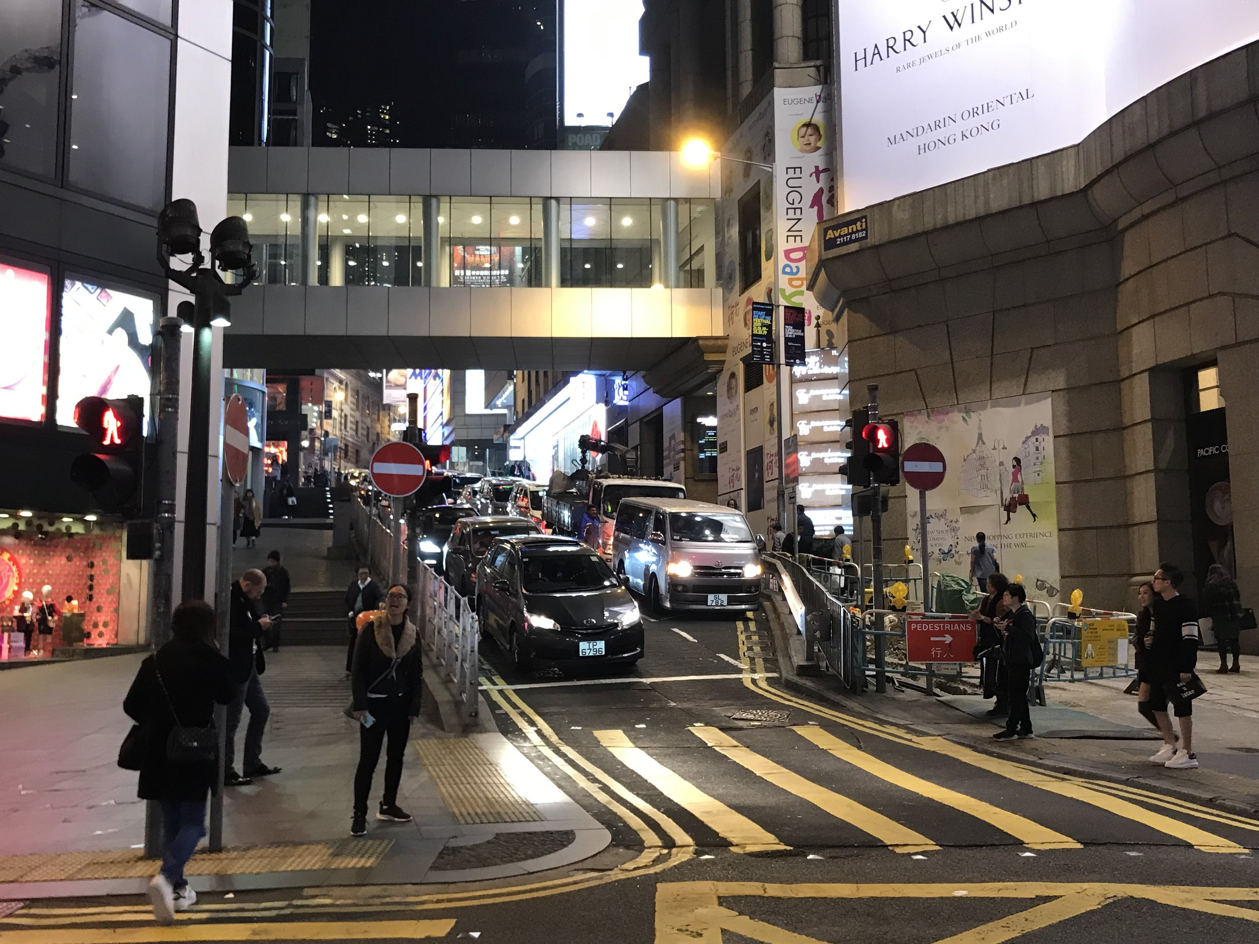 Một con đường băng ngang trên phố đảo Hong Kong với xe cộ lưu thông qua lại.
