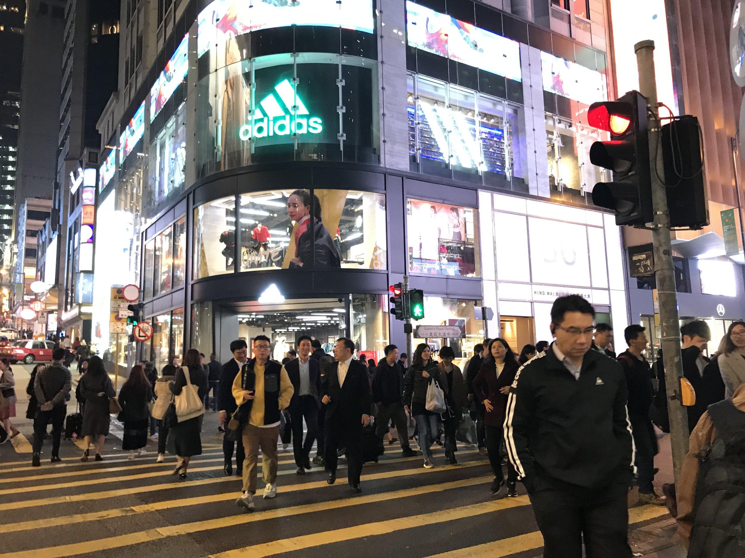 Đảo Hong Kong sống động về đêm dưới ánh đèn và khách du lịch cùng người dân hòa trong đoàn người đi mua sắm.