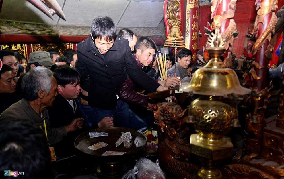 Nhảy bổ lên cả lư đồng, bàn thờ để cướp bằng được một chút lộc mang về nhà tại đền Trần (Ảnh: Zing)