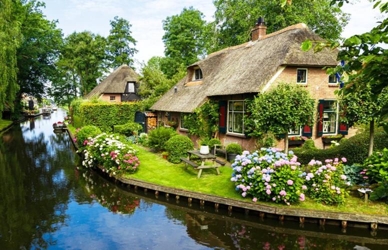 Những ngôi nhà được thiết kế đơn giản bên khu vườn và dòng sông trước mặt.